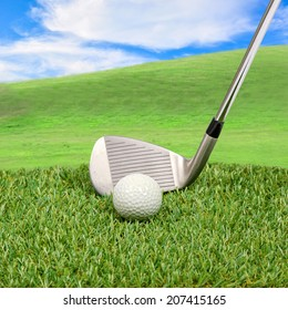 Golf ball and golf club with hill background