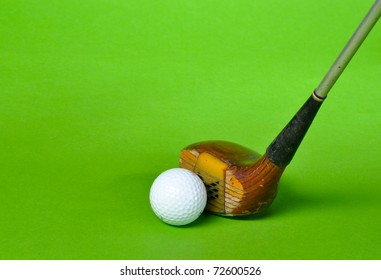 Golf ball and club isolated on green background with copy space