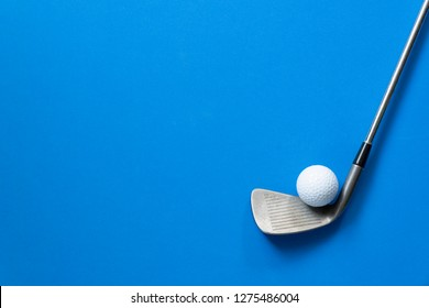 golf ball and golf club on blue background