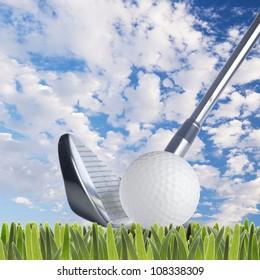 Golf ball and golf club on fresh green grass