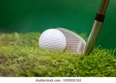 Golf ball and golf club are on green grass background
