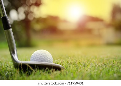 The golf ball and golf club with the warm light of the evening.