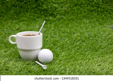 Golf ball with cup of tea on green grass, drink for golfer at club house