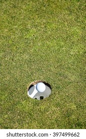 Golf Ball Dropping in Air over the Edge of the Cup