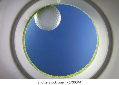 Golf ball drops into a cup on green, shot from the bottom of the hole, created  in studio