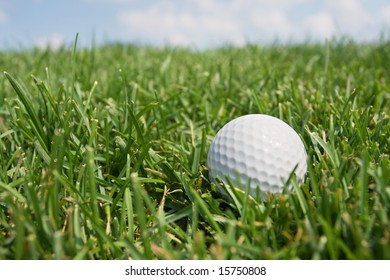 Golf Ball in Fairway Grass against blue sky and clouds.
