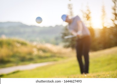 A golf ball floating in the air and Blurry golfer in the background.
