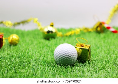 Golf ball with golden box ornament are on green grass for golfer's Christmas holiday