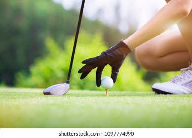 golf ball in hand of woman takes on to wooden tee on tee off of the golf course, ready to hit away to the destination fairway forward