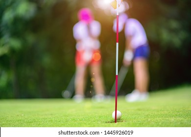 golf ball hit or putt by the woman player at mostly run through the hole on the green of the golf course, missed the target of putting golf ball to the target of golf hole