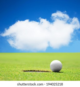 golf ball at the hole with beautiful sky