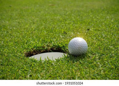 Golf ball and golf hole on green grass. A golf ball sits at the lip of the hole on the putting green. white golf ball near hole on fairway with the green background in the country side.
