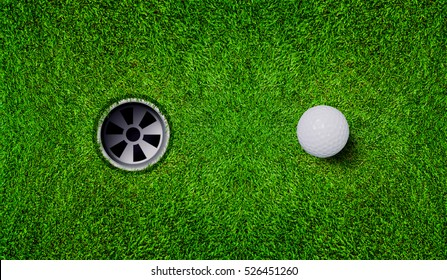 Golf ball and golf hole on green grass.