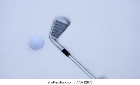 A golf ball and iron on the snow.