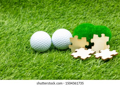 Golf ball and jigsaw are on green grass with love