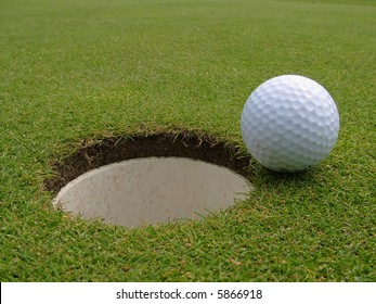 A golf ball just short of going into the hole