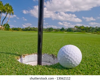 golf ball lies just at lip of the hole