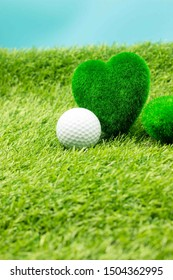 Golf ball with love heart shape are on green grass