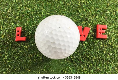 Golf ball with love letter on green course.  A golf ball beside a cup A golf ball is a special ball designed to be used in the game of golf.