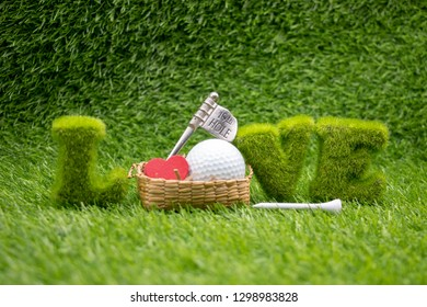 Golf ball with love shape and white tee on green grass for golf lover