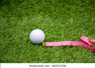 Golf ball with measuring tape on green grass