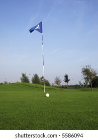 golf ball near hole with flag and number