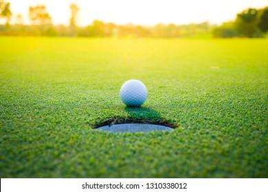 golf ball near hole on green grass