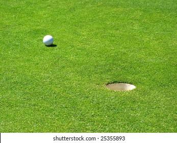 Golf ball near the hole on the green