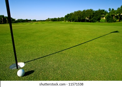 golf ball near hole and pin of lovely tropical golf course with clear blue sky