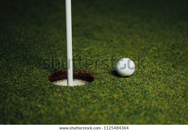 golf ball nearby hole with pin flag, green grass background, closeup view