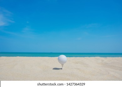 golf ball on beach sand under blue sky background