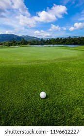 Golf ball on course, beautiful landscape with mountains on background