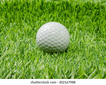 Golf ball on course with green grass.