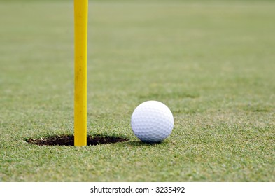 golf ball on the edge of the cup, shallow DOF