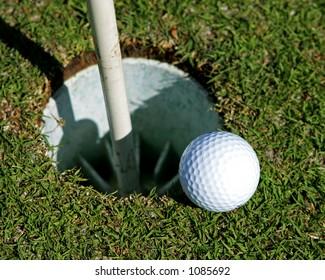 Golf Ball on the edge of a hole
