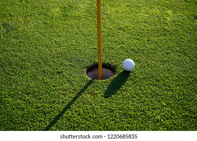 Golf ball on the edge of hole on putting green on golf course