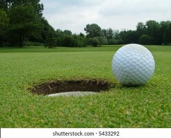 A Golf Ball on the edge of the hole
