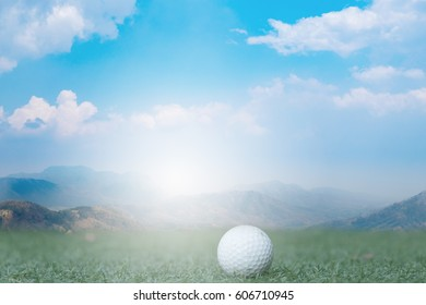golf ball on fake green grass with landscape and sunlight background