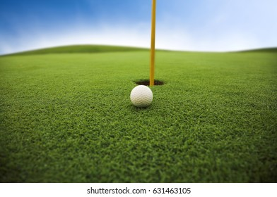 golf ball on field close up. Shallow depth of field and focus on ball. Some dew drops are visible on grass.