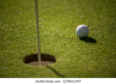 Golf ball on the green by the hole