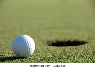 golf ball on the green close to the hole