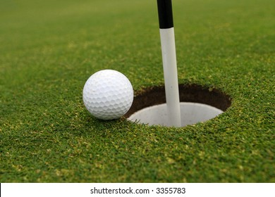 Golf ball on green close to cup with flag pole in it.