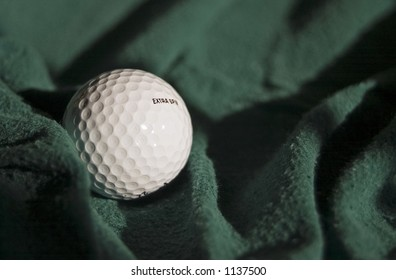 """Golf ball on green fabric with the words """"extra spin"""" on the ball."""