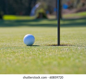Golf ball on green with flag. Shallow depth of field. Focus on the ball.