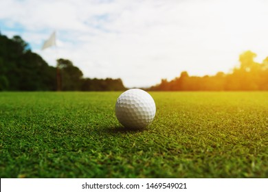 golf ball on green grass with hole and sunlight