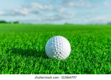 Golf ball on green grass in golf course with blu sky and copy space.