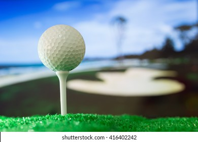 Golf ball on green grass. The background is a golf course.