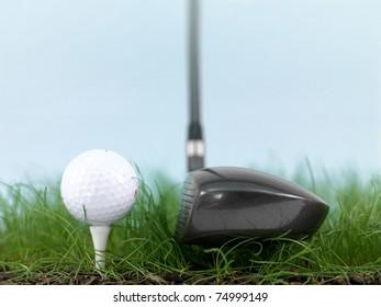 A golf ball on green grass isolated against a blue sky