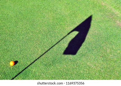 Golf ball on the green with shadow of the flagstick.