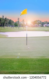 The golf ball on the green is waiting for the athlete to hit the hole and the flag to reach the goal.